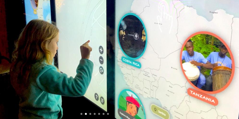 a girl touching a wall mounted screen