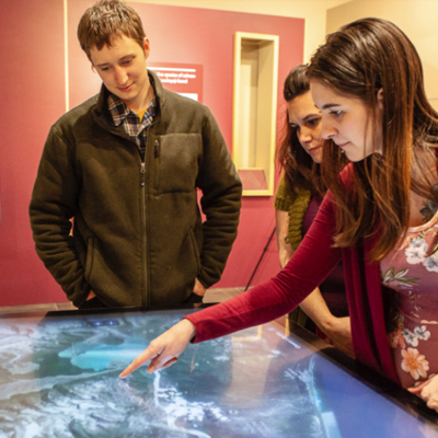 3 people interacting with a touch screen map