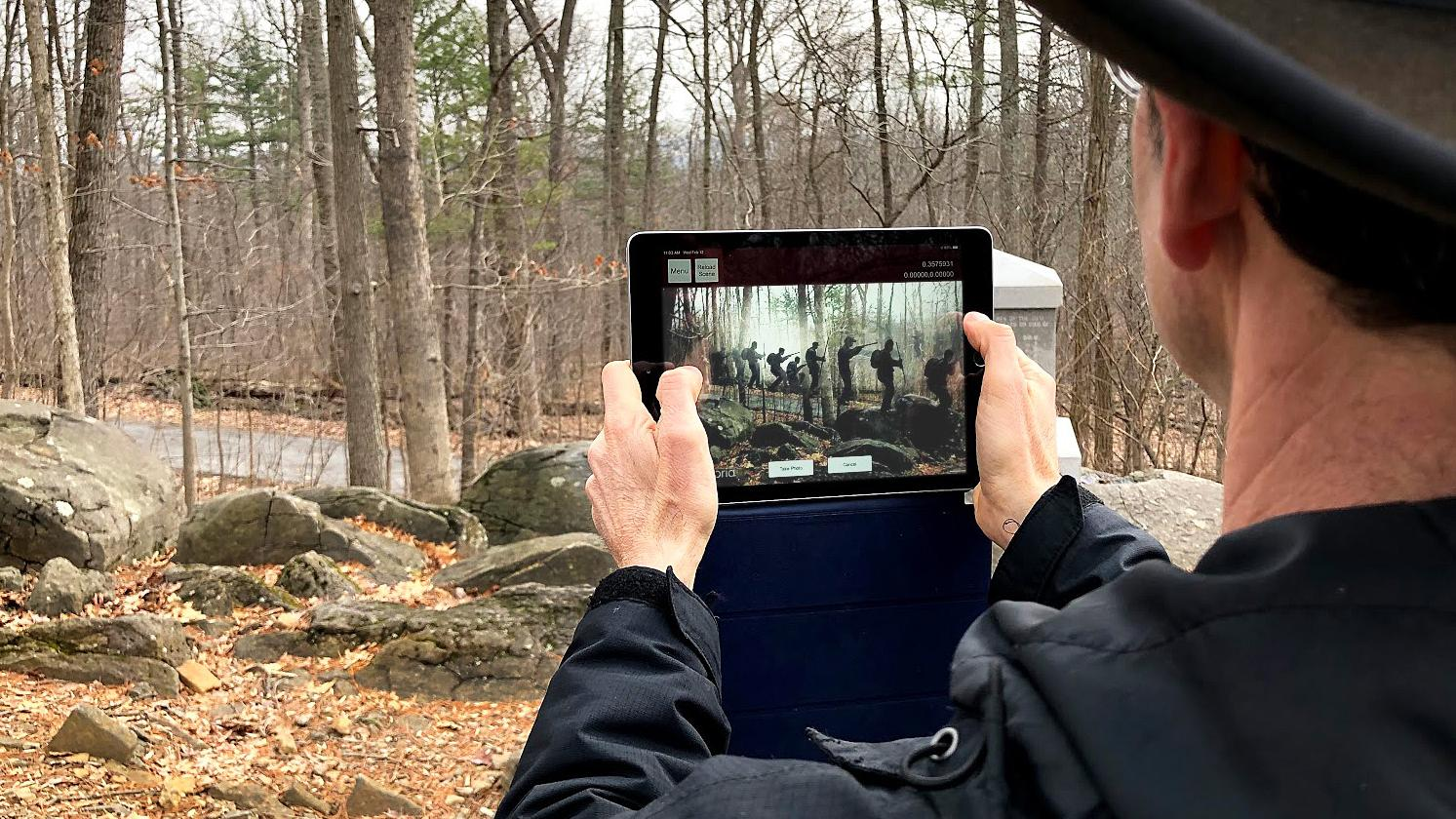 Man holding an iPad that is displaying an Augmented Reality application.