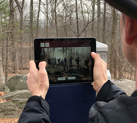 a man holding an iPad looking at an AR battle scene in the woods