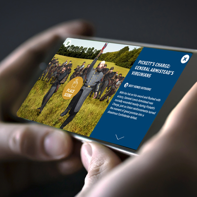 a photo of hands holding a smart phone horizontally and displaying a scene for Pickett's Charge