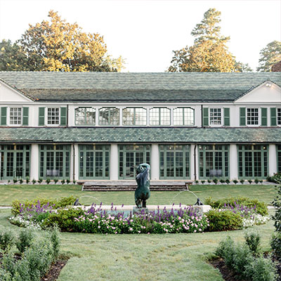 a small pond with a statue sits in front of a large white country house with green shutters